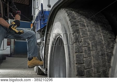 Caucasian Truck Driver Or Trucker In His 40s Preparing His Semi Truck Or Lorry For Heavy Duty Vehicl