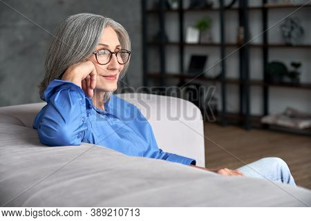 Beautiful Relaxed Mature Old Woman Relaxing Sitting On Couch At Home. Peaceful Middle Aged Grey-hair