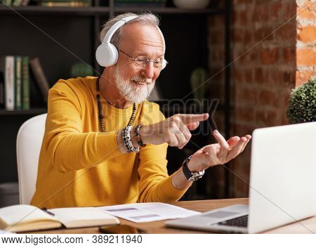 Happy Elderly Male Freelancer In Headphones Talking And Bending Fingers While Making Video Call To C