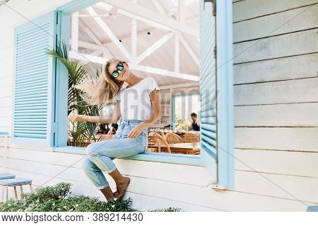 Graceful Fair-haired Girl In Vintage Jeans Posing On Window Sill. Inspired Tanned Young Lady Wears S