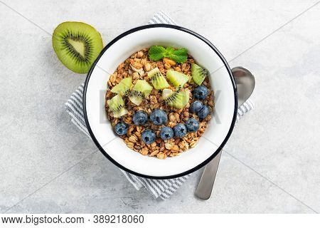 Oat Granola With Fruits In Bowl On Concrete Background. Kiwi And Blueberries With Crunchy Oat Honey