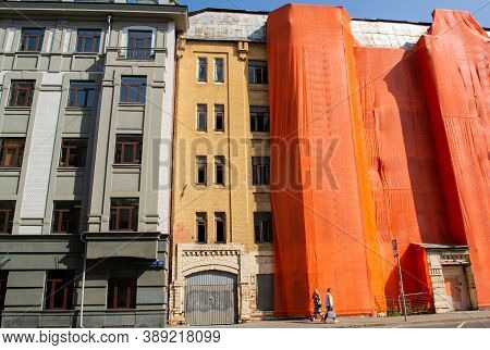 Moscow, Russia, September 2019: The Old Brick Building Is Covered With An Orange Cloth For Reconstru