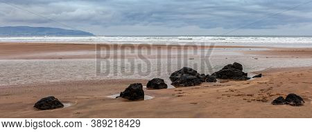 Layers Of An Incoming Tide And Ridge Of Large Stones On The Downhill Beach In The Downhill In County