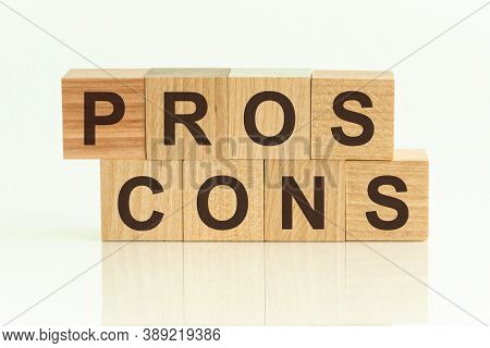 Pros Cons - Text On Wooden Cubes On A White Gradient Background.