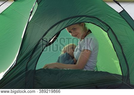 Mom Is Breastfeeding Her Baby In Camping Tent. Camping With Children.