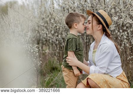 Happy Mother And Son Having Fun Together. Mother Gently Hugs Her Son. In The Background White Flower