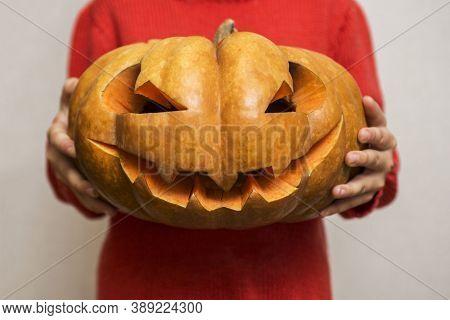 Halloween. Carved Orange Pumpkin On Kid Hands, Jack-o-lantern Traditional Symbol Of Halloween. Child