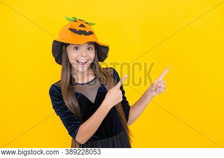 Child In Gourd Hat Pointing Finger On Copy Space. Kid Wearing Squash Headwear. Carnival Costume Part