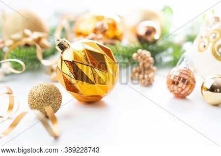 Christmas Background In Green-gold Tones With Bokeh Effect. Gold Christmas Ball With Decor On A Whit