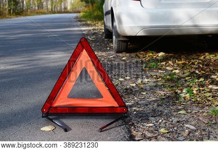Warning Stop Sign On The Road Against The Background Of A White Car And Forest. Concept Of Roadside