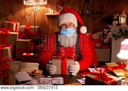 Old Funny Bearded Santa Claus Wearing Face Mask, Holding Gift Box Preparing For Xmas Eve Sitting At