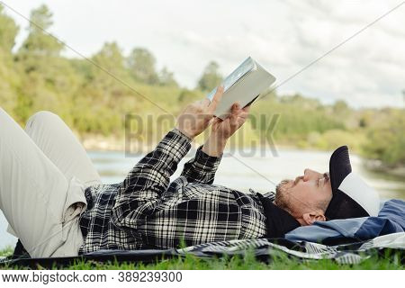 Young Man Lying On The Grass By The River While Reading Book. Relaxation And Springtime Concept