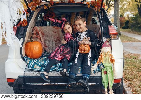 Trick Or Trunk. Siblings Brother And Sister Celebrating Halloween In Trunk Of Car. Children Kids Boy