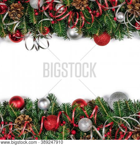 Christmas border frame design copmosition of fir tree branch and red silver decorations balls baubles ribbon pine cones isolated on white background