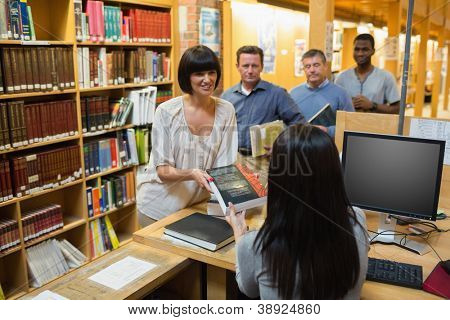 Librarian handing book to woman at library desk