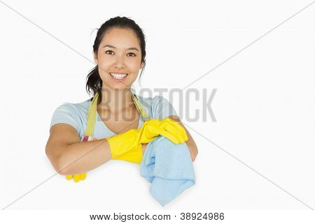 Smiling woman in apron and rubber gloves leaning on white surface with a rag