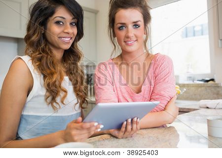 Happy friends with tablet computer having coffee in kitchen