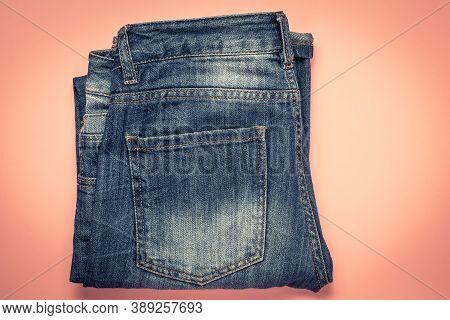 Blue Frayed Jeans With A Pocket, Folded Shabby Pants On A Pink Background. Dark Denim