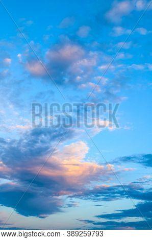 Blue sky background, white dramatic pink clouds lit by sunset light. Vast sky landscape scene. Blue sky background, vast sky landscape, sky scene with dramatic clouds.