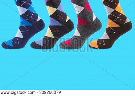 Four Legs In Socks With A Pattern Of Colored Rhombuses, On A Turquoise Background, Concept