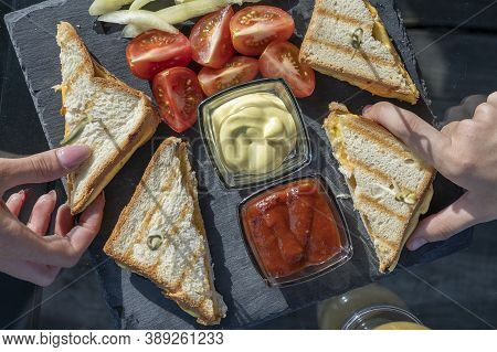 Two Girls Holding Club Sandwich With Ham, Cheese And Red Tomato On A Black Slate Plate. Ham Cheddar