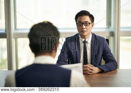 Nervous Young Asian Man Being Interviewed By Corporate Human Resources Manager