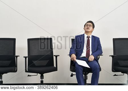 Older Asian Male Job Seeker Looking Up To The Ceiling While Waiting In Line For Interview