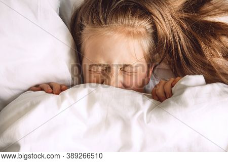 Child Hiding Under Duvet In Bed. Morning Routine. Indulge In The Bedroom In The Morning. The Girl Cl