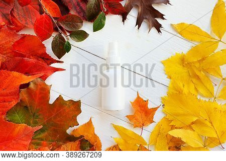Mockup Of White Plastic Spray Bottle And Bright Autumn / Fall Leaves Frame. Natural Organic Spa Cosm