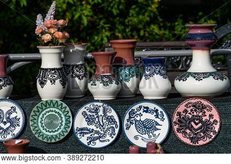 Many Hand Made Plates And Other Pottery Objects With Traditional Decorations Displayed For Sale As S