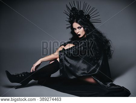 Halloween Theme: Beautiful Young Witch Dressed In Black Cloak And Headgear With Roses And Spikes. Da