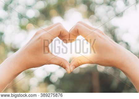 Female Hands Heart Shape On Nature Bokeh Sun Light Flare And Blur Leaf Abstract Background. Copy Spa