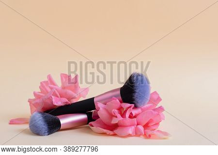 Two Makeup Brushes Lie On Pink Rose Flowers. The Concept Of Softness And Tenderness Of Cosmetics And