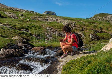 Female Hiker Near The Wild Splashing Waterfall
