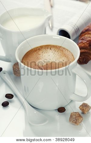breakfast with coffee, croissant and magazine