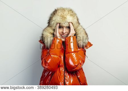 Young Girl In A Red Jacket And A Fur Hat, Closed Her Eyes With Her Hands And Opened Her Face On A Li