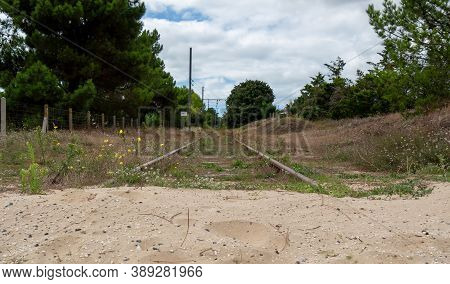 An Abandoned Railroad Track With The Sand