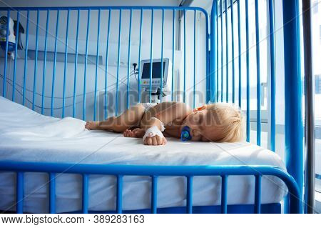 Little One Year Old Toddler Sleep In Hospital With Catheter In His Hand And Pacifier
