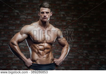 Bodybuilder Strong Man Pumping Up Abs Muscles