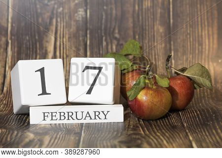 February 17. Day 17 Of Month. Calendar Cube On Wooden Background With Red Apples, Concept Of Busines