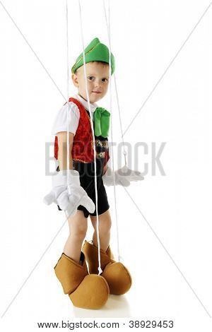 An adorable preschool Pinocchio marionette standing with strings and all.  On a white background.