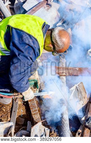 Worker Is Cutting Scrap Metal With Acetylene Torch Wearing Protective Goggles On His Head.
