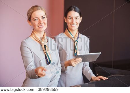Portrait Of Two Smiling Flight Attendants Handing Tickets To Passenger While Standing At Check In De