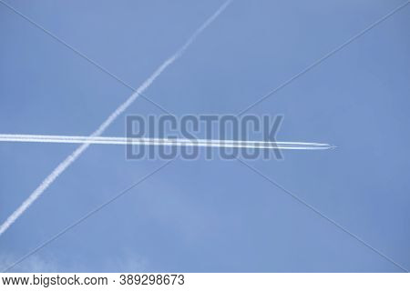 Long white planes traces crossing in the clear cloudless blue sky and big passenger supersonic airplane with four jet engines flying high