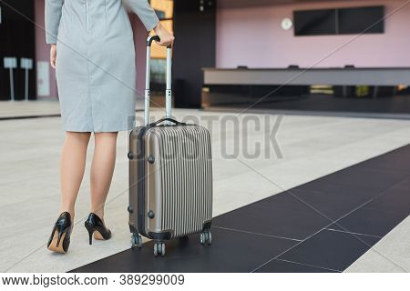 Low Section Portrait Of Elegant Young Woman Wearing High Heels Heels Walking With Airport With Suitc