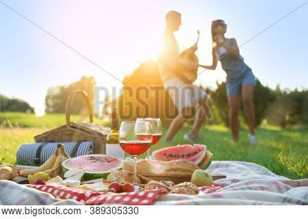 Happy Couple Having Fun On Picnic In Park, Focus On Blanket