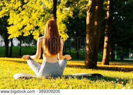 Rear View Of Slim Young Redhead Woman Meditating In Lotus Pose Holding Hands On Knee In Om Position,
