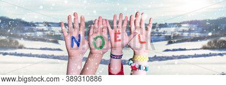 Children Hands Building Word Noel Means Christmas, Snowy Winter Background