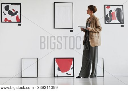 Full Length Portrait Of Creative Elegant Woman Looking At Paintings Hanging On White Wall While Visi