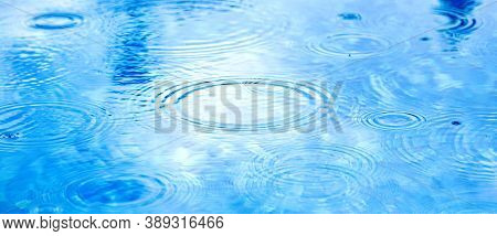 Stains Circles On Water From Rain. Raindrops On Pool Blue Water Surface. Blue Water Texture As Backg